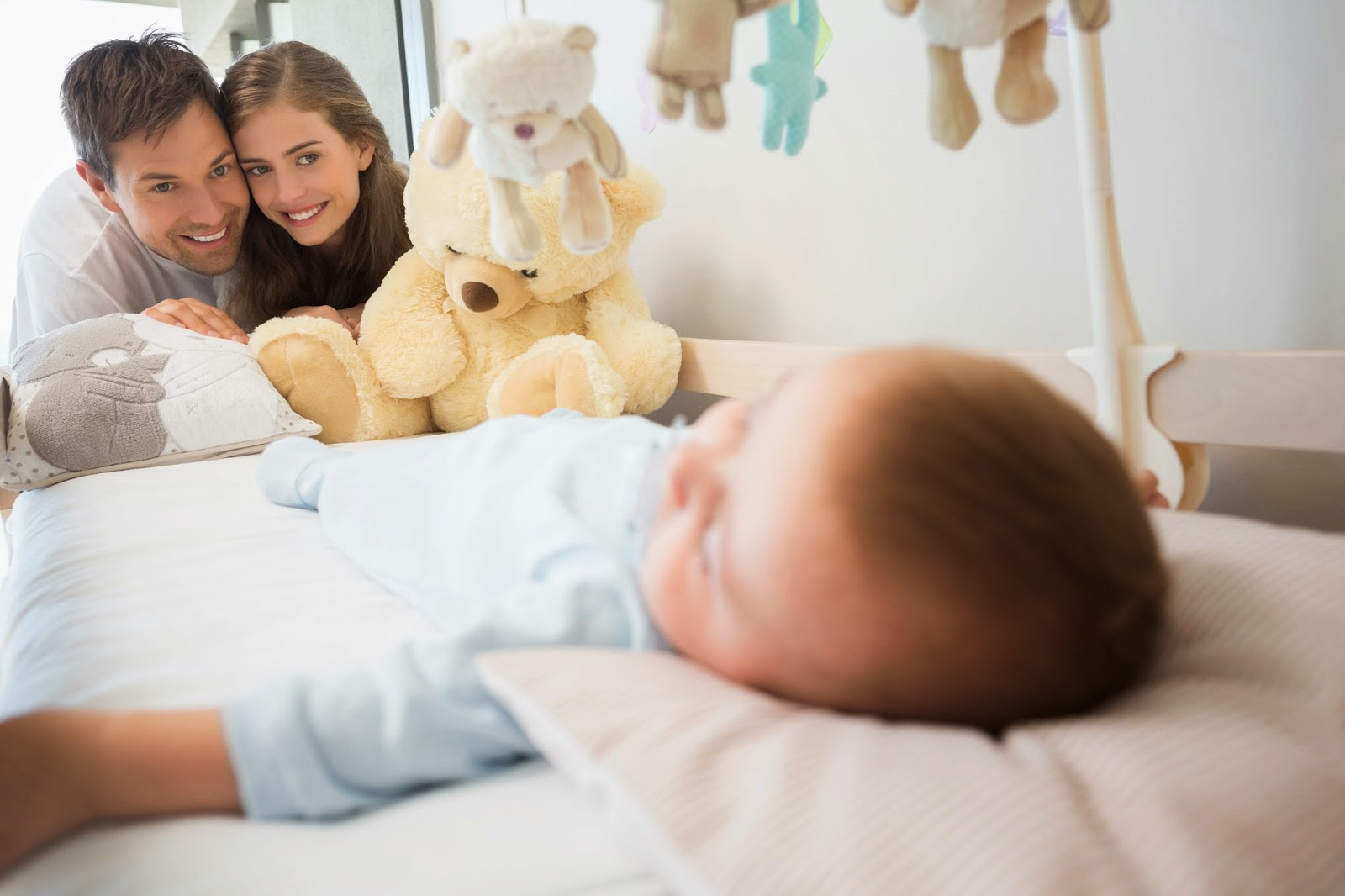 Счастливые родители у кроватки младенца