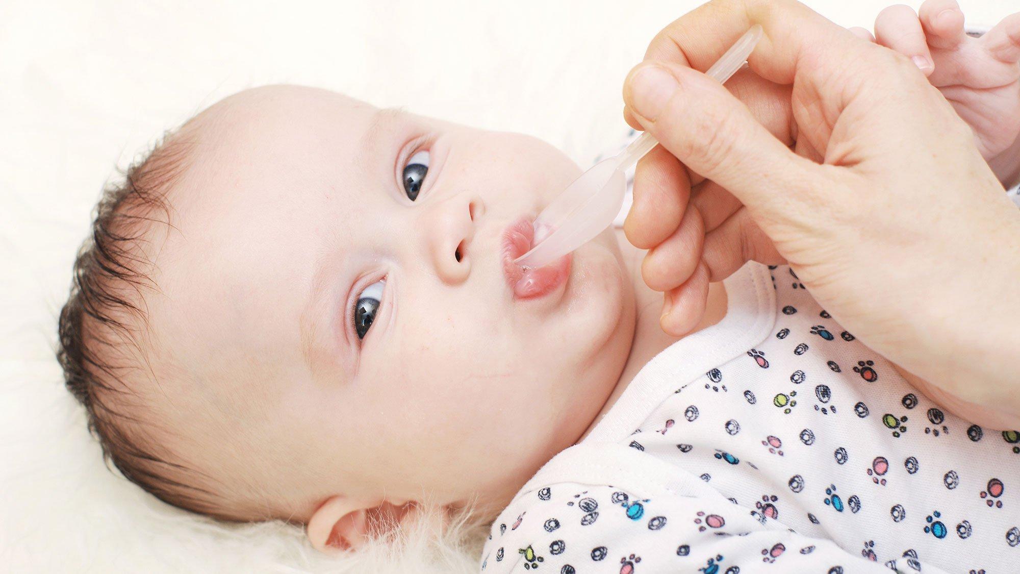 Младенцу дают сок из ложечки