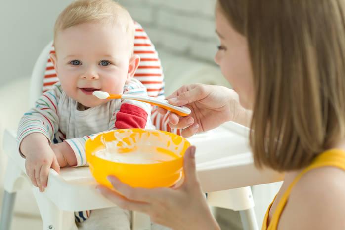 Ребенок пробует новую еду с тарелки