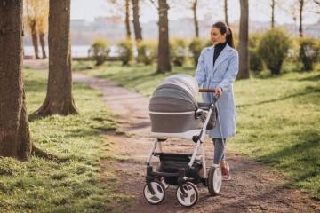 Мама гуляет с коляской в парке