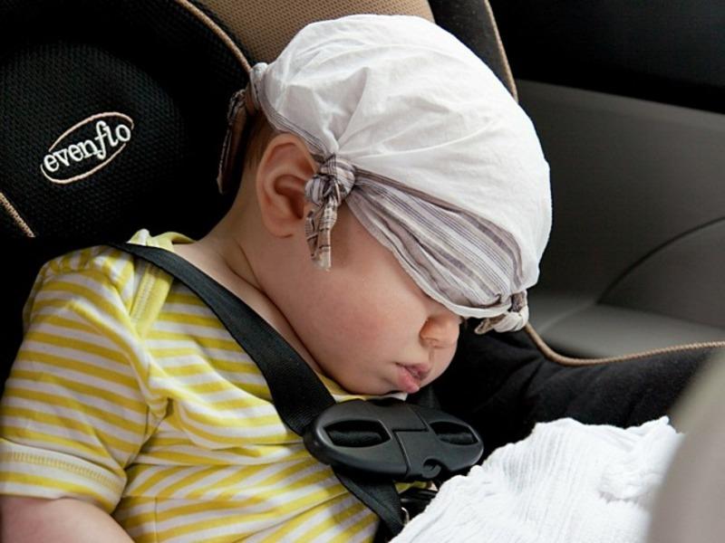 Грудничок спит в машине с платочком на голове