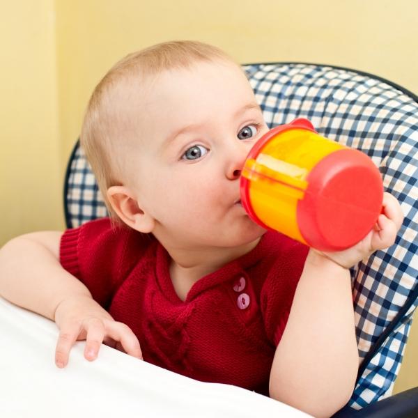 Малыш пьет из поилки