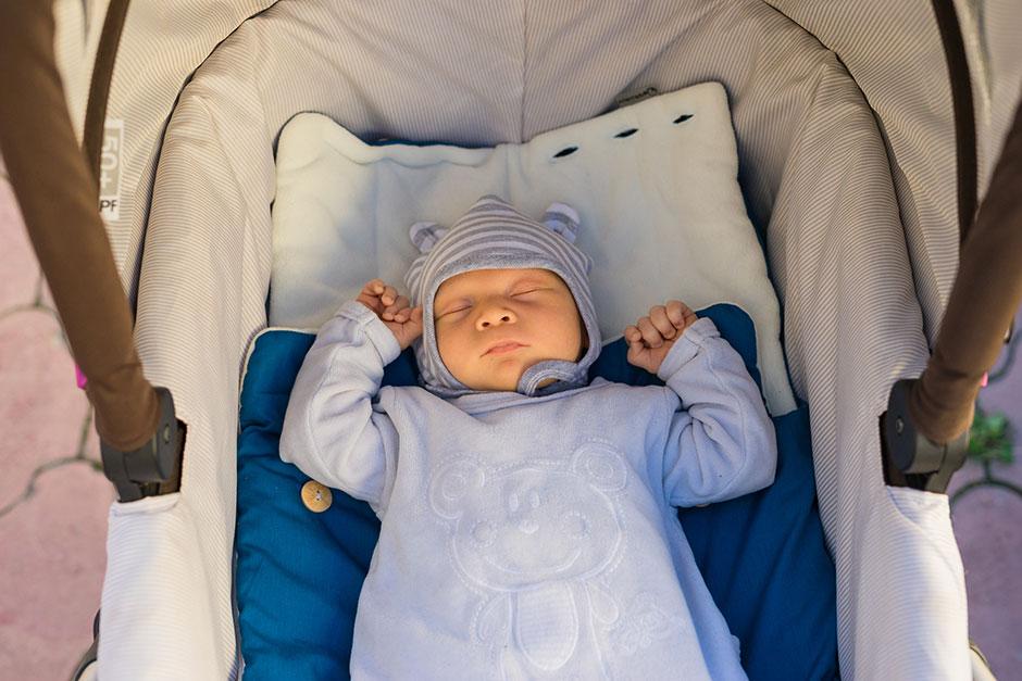 Новорожденный в коляске спит