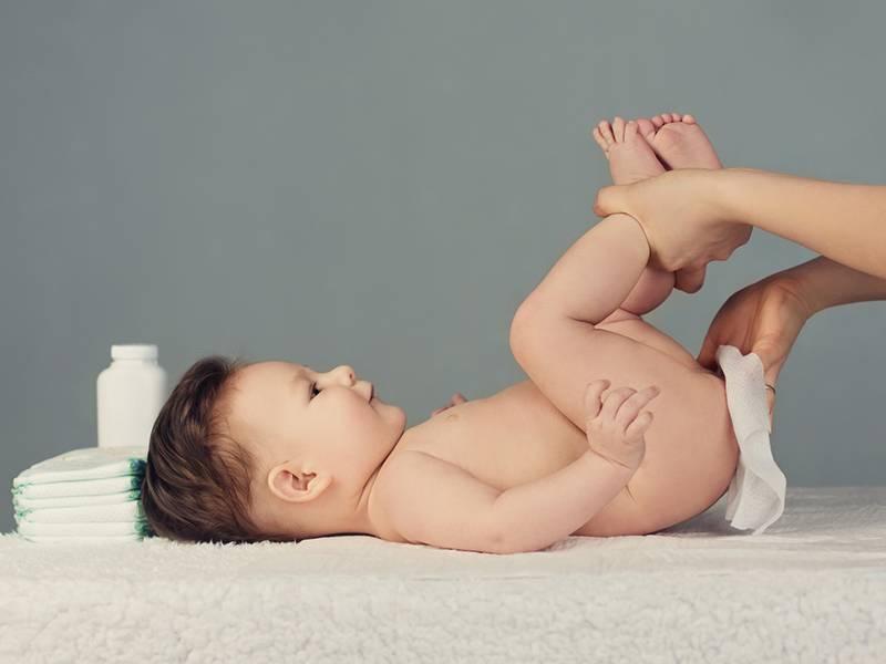 Ребенку вытирают попу полотенцем