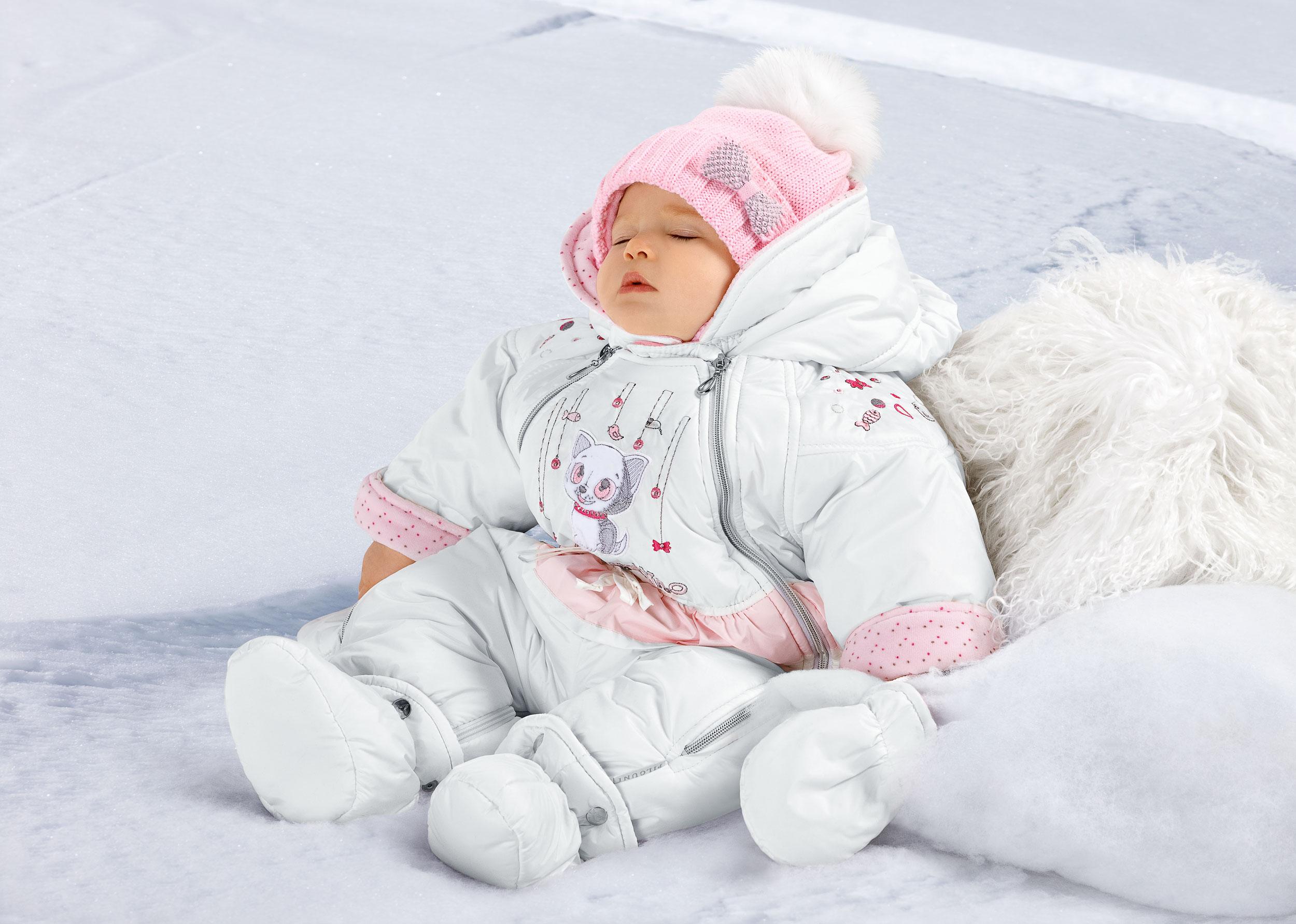 Грудничок в комбинезоне на снегу
