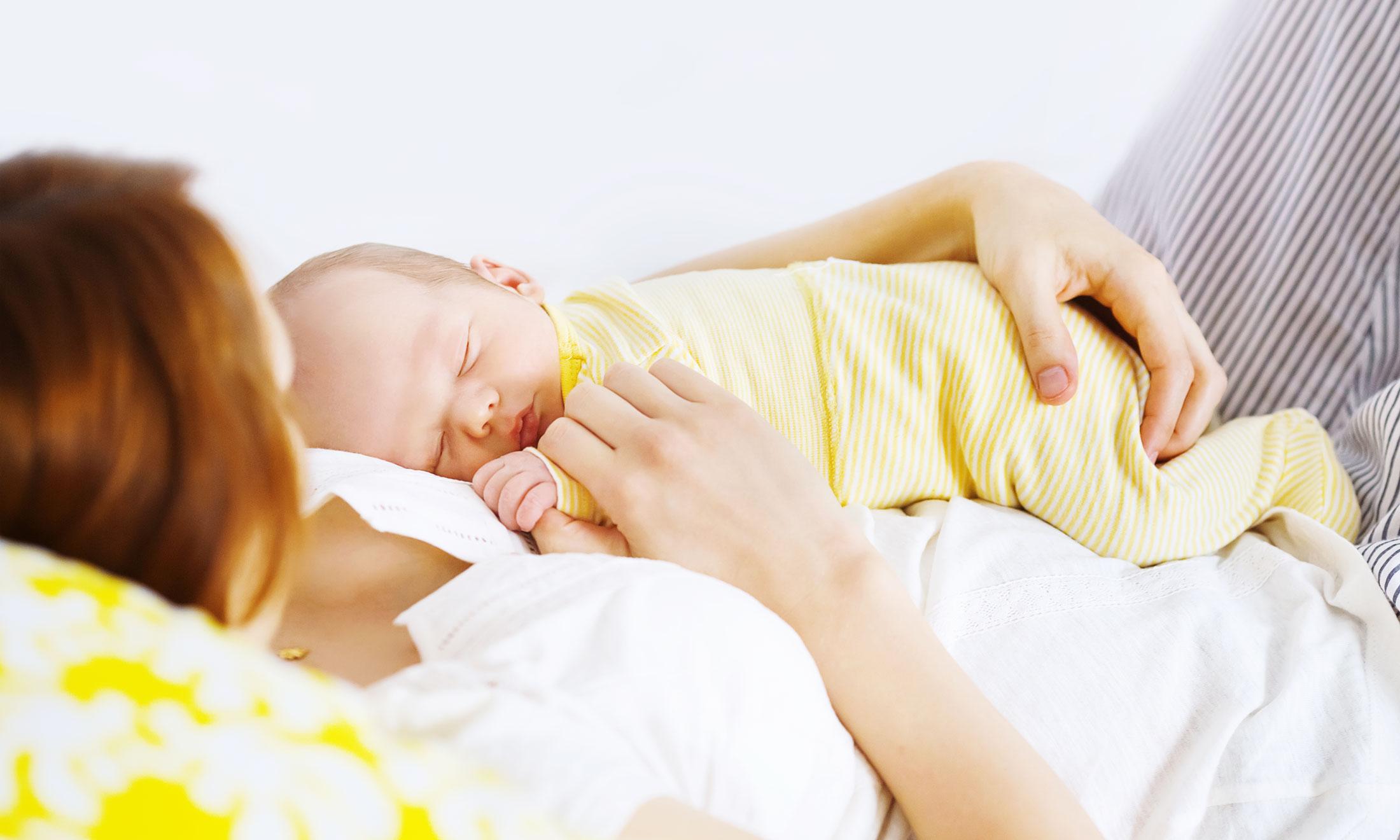 Грудничок спит на руках у мамы