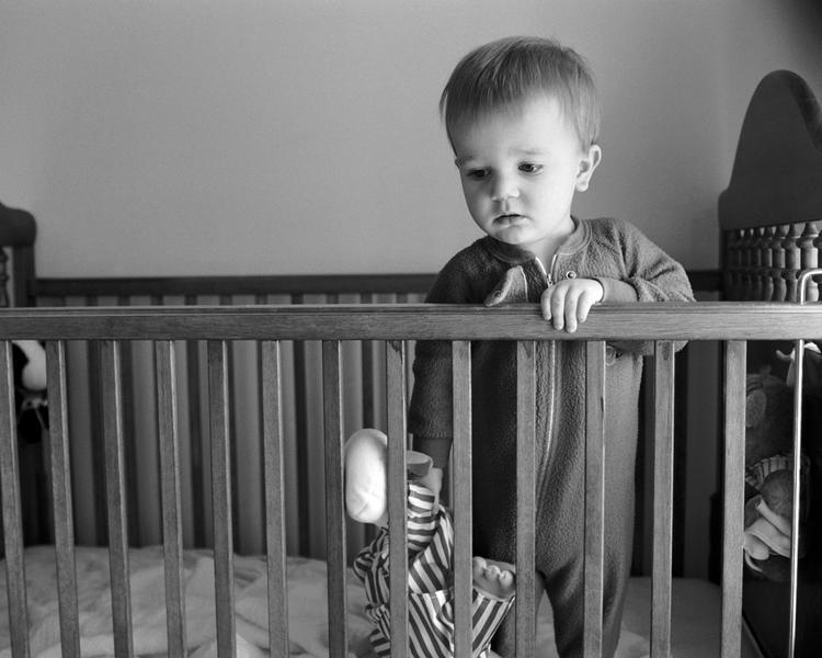 Малыш стоит в кровати