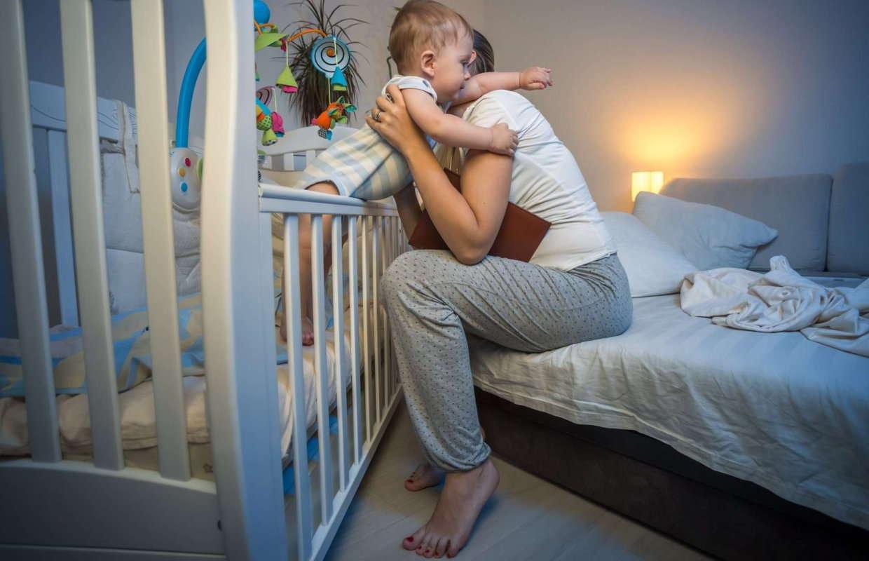 Мама приучает ребенка спать в кроватке