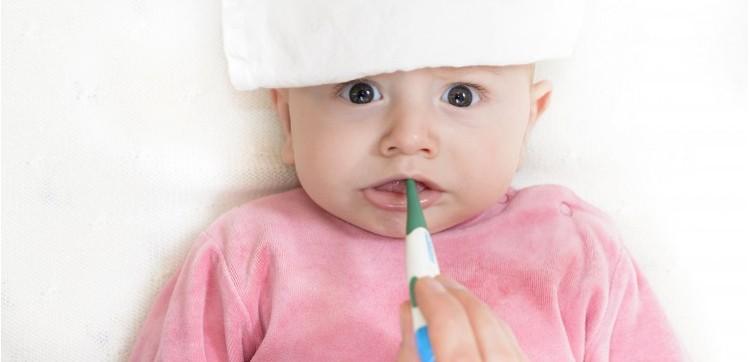 Мама измеряет температуру младенцу