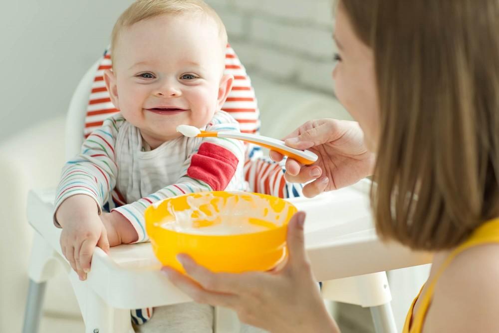 Ребенка кормят кашей