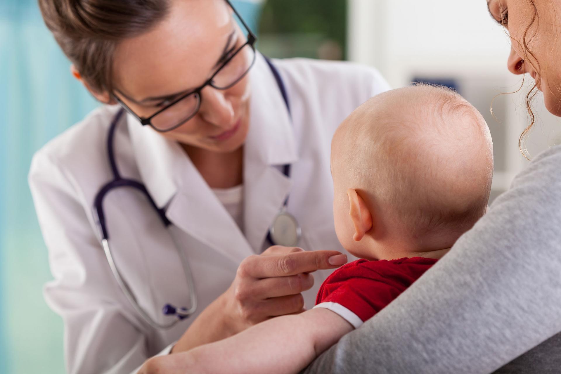 Специалист осматривает младенца