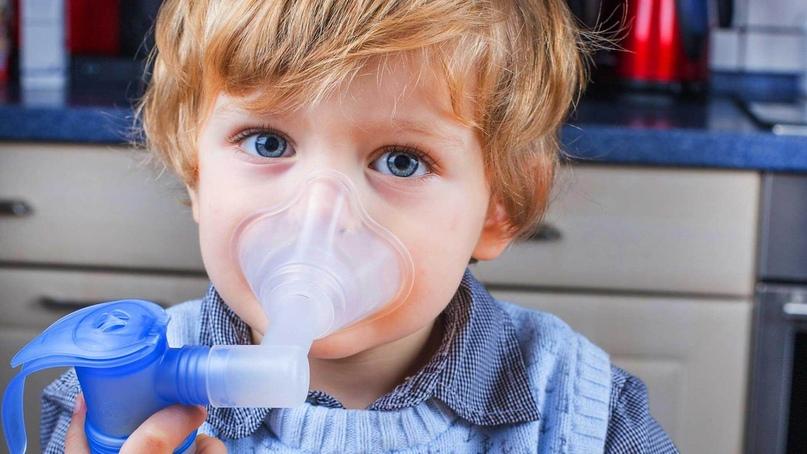 Мальчик дышит ингалятором