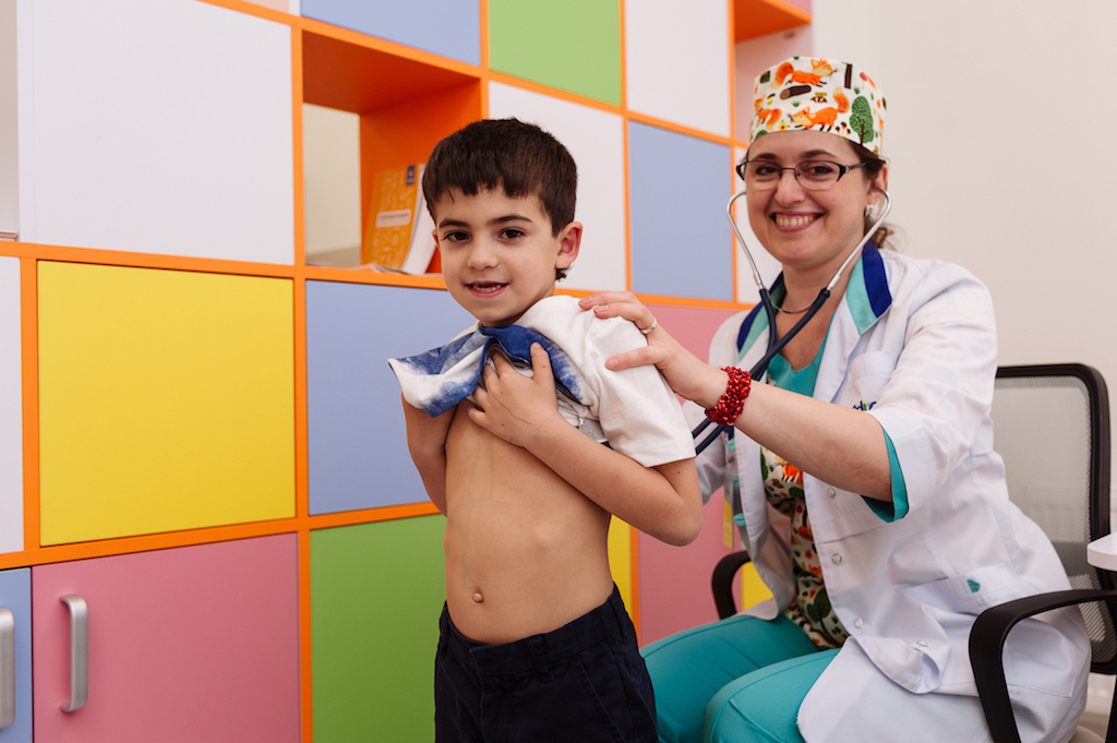 Мальчика слушает врач