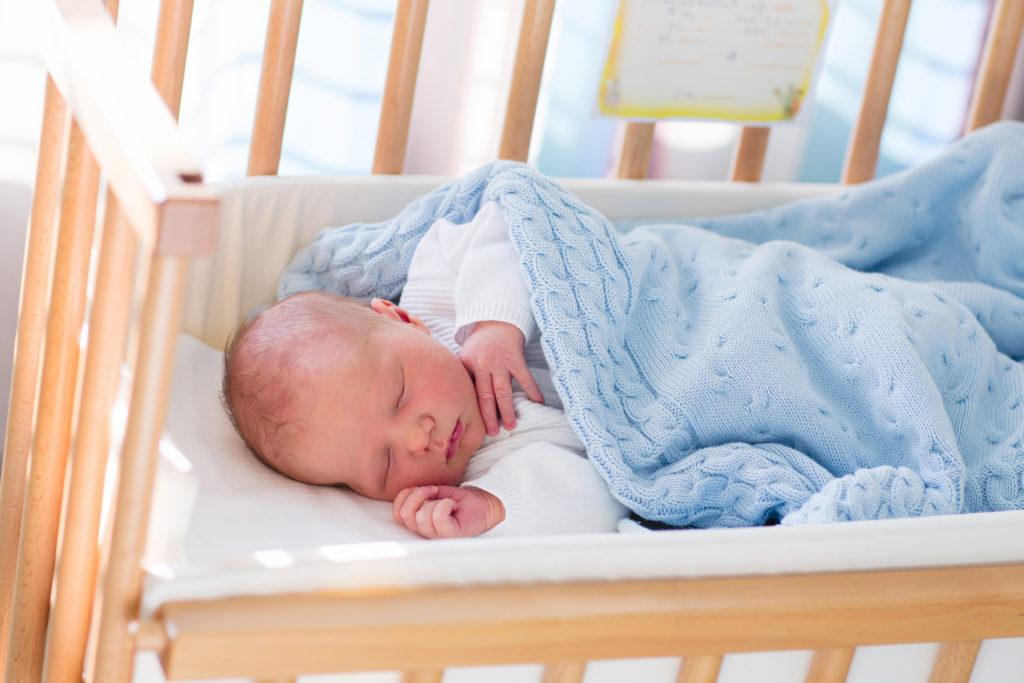Младенец один в кроватке