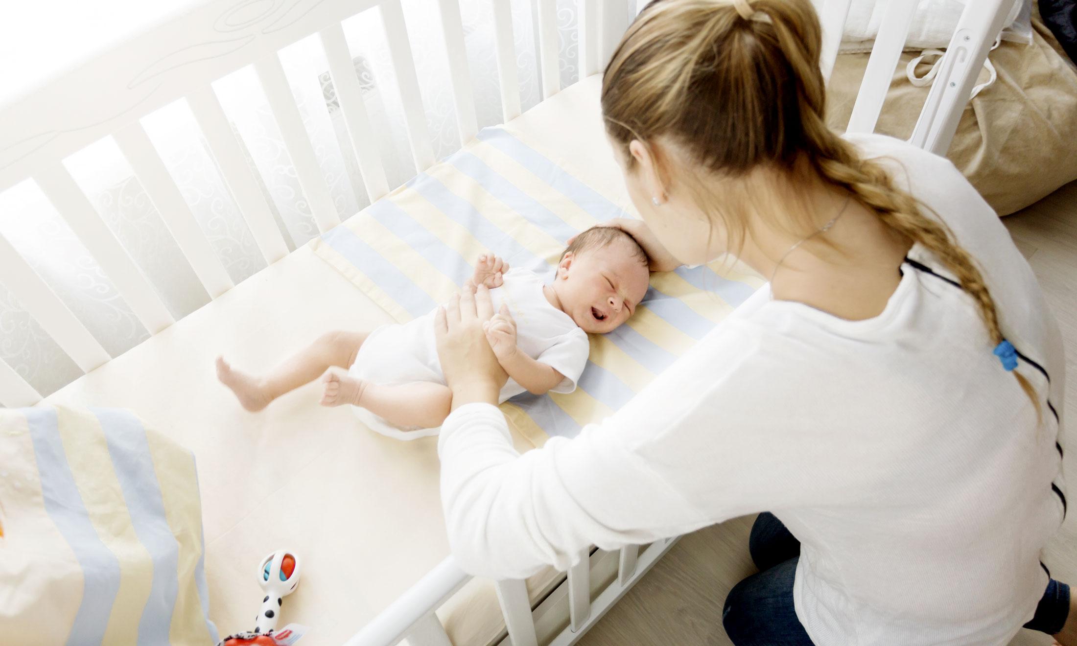 Применяя «метод стула» мама успокаивает дитя в кроватке прикосновениями и голосом