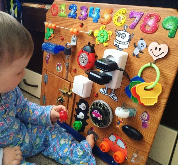 Малыш играет с бизибордом
