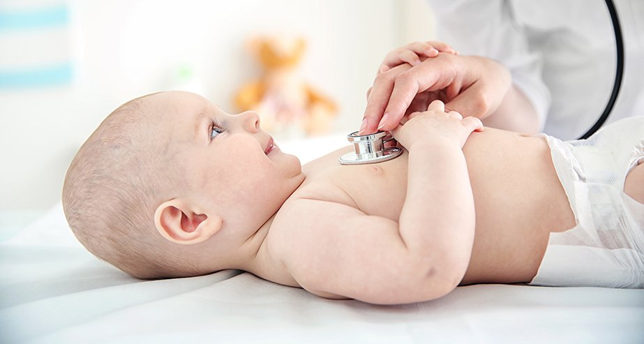 Педиатр осматривает новорожденного