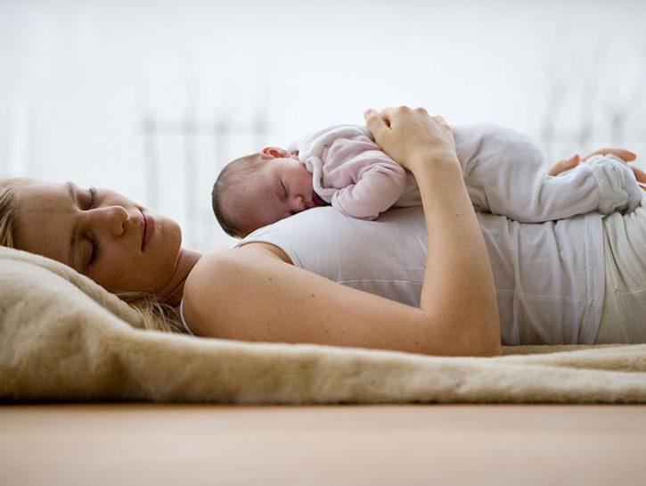 Младенец спит на материнском животе