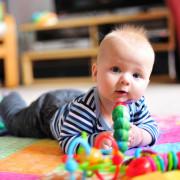 Годовалый ребенок играет на коврике